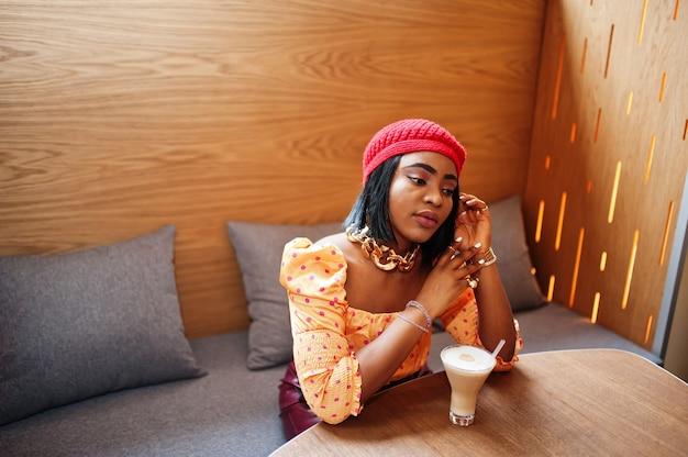 Elegante mujer afroamericana en boina francesa roja, blusa de lunares con cadena de cuello dorado grande pose interior