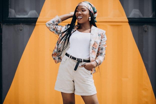 Elegante mujer afroamericana por la pared de color
