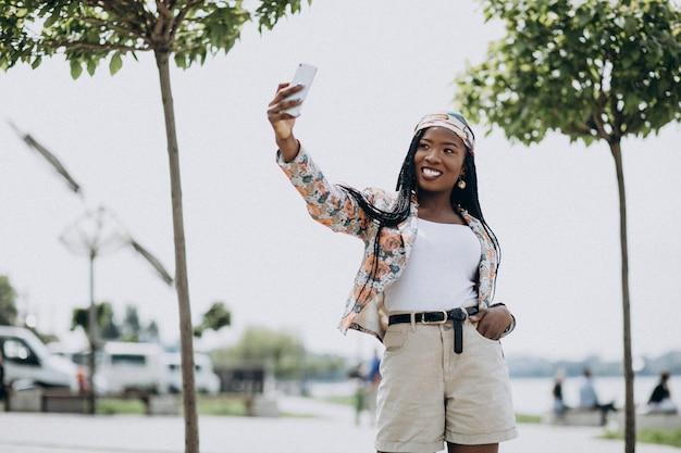 Elegante mujer afroamericana en el parque haciendo selfie