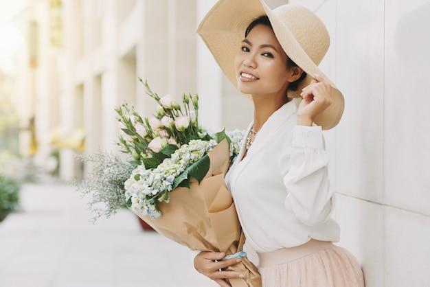 Elegante mujer asiática bien vestida en gran sombrero para el sol posando en la calle urbana con flores.