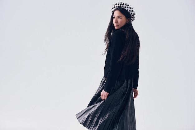 Elegante mujer asiática en boina y falda negra de moda