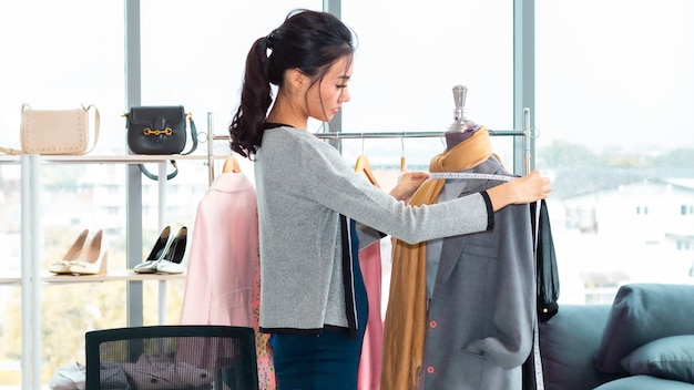 Elegante mujer asiática diseñadora de modas y sastre trabajando en tienda de ropa