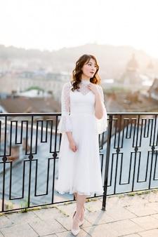 Elegante mujer asiática en vestido blanco de pie en la terraza de la azotea