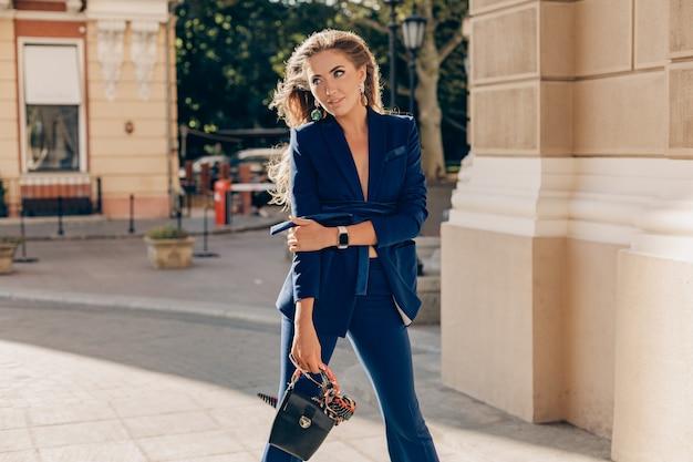 Elegante mujer atractiva vestida con elegante traje azul y gafas de sol caminando en la calle sosteniendo el bolso