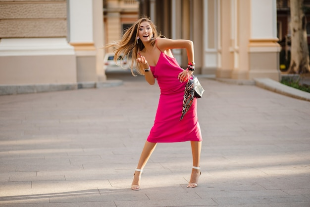 Elegante mujer atractiva con vestido de verano sexy rosa caminando en la calle sosteniendo el bolso
