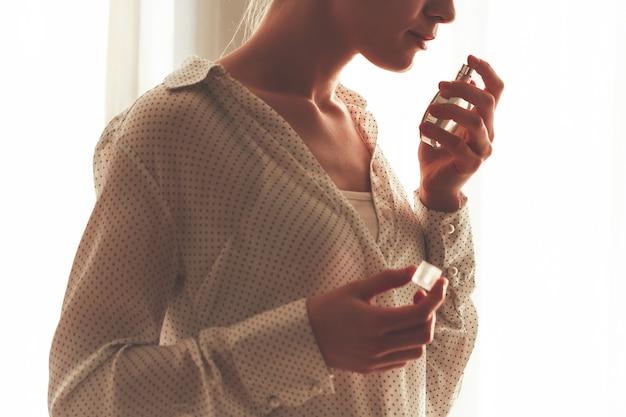 Elegante mujer en blusa con botella de perfume favorito.