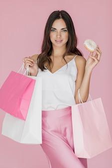 Elegante mujer con bolsas de compras y una rosquilla