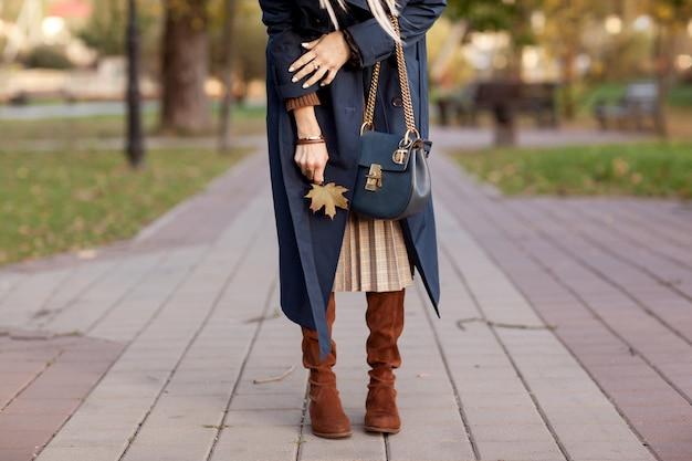 Elegante mujer camina en el parque otoño.
