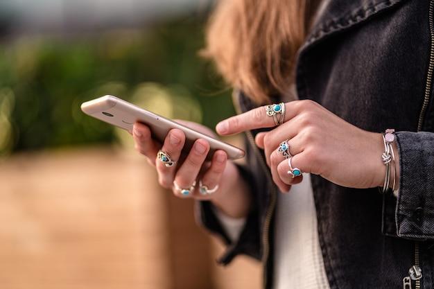 Elegante mujer casual que usa un teléfono inteligente para redes sociales, navega y chatea en línea con amigos mientras camina por la ciudad