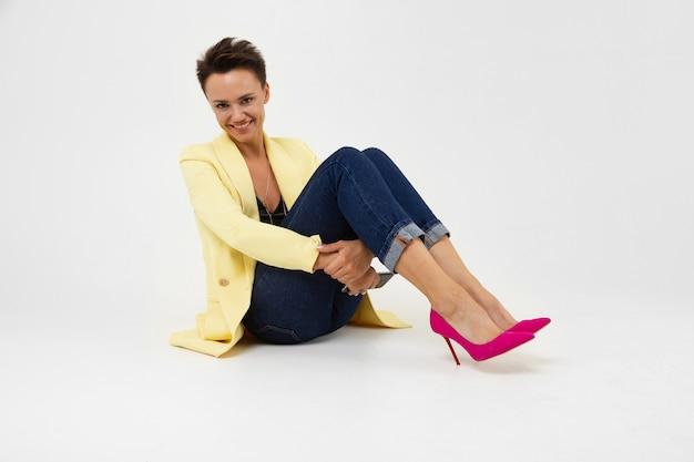 Elegante mujer con una chaqueta de limón sobre un fondo blanco se sienta sosteniendo sus manos debajo de las rodillas