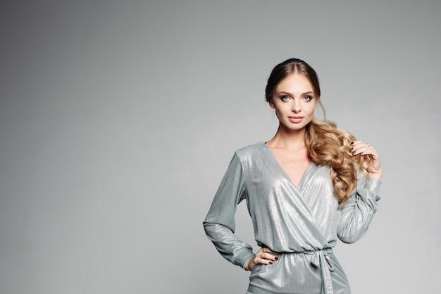 Elegante mujer confiada posando con pelo rizado en la mano.