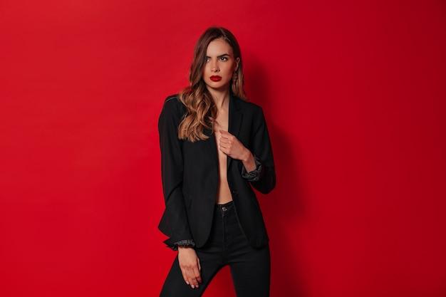 Elegante mujer confiada en traje negro posando sobre pared roja