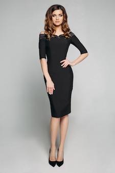 Elegante mujer delgada en vestido negro clásico y tacones.