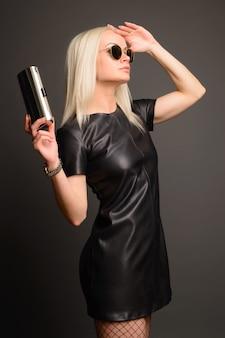 Elegante mujer elegante en vestido de cuero negro con bolso plateado pequeño