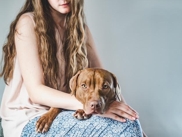 Elegante mujer y un encantador cachorro. de cerca