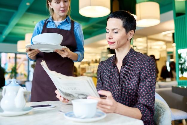 Elegante mujer esperando comida en la cafetería