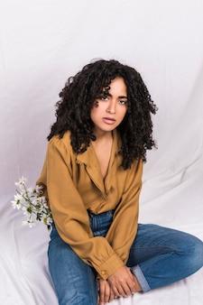 Elegante mujer étnica con flores en jeans.