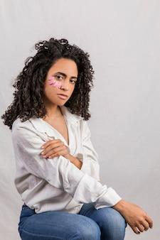 Elegante mujer étnica con pétalos en la cara.