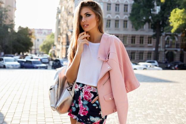 Elegante mujer europea rubia en chaqueta de cuero rosa posando al aire libre.
