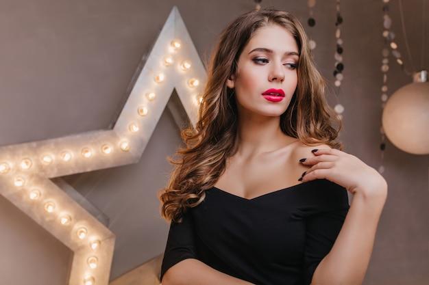 Elegante mujer europea en vestido con hombros abiertos mira pensativamente hacia otro lado. cerrar retrato de dama espectacular en la pared de la estrella brillante