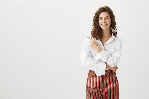 Elegante mujer exitosa apuntando a la izquierda y sonriendo