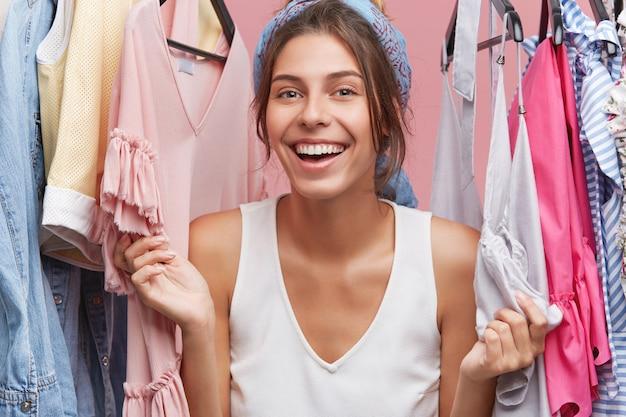 Elegante mujer con feliz emocionada sonrisa mientras está de pie entre la ropa de moda de verano, disfrutando de los precios de venta durante las compras en el centro comercial de la ciudad. estilo, moda, consumismo y concepto de compra.