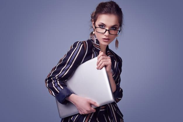 Elegante mujer glamour en traje de moda y gafas con cuaderno