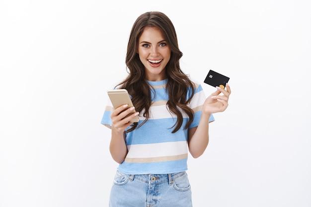 Elegante mujer guapa haciendo un pedido, pagando compras en línea con tarjeta de crédito, sosteniendo el teléfono inteligente sonriendo alegremente, explicando lo fácil que es hacer compras en internet, pared blanca