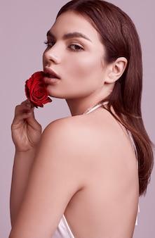 Elegante mujer hermosa en un traje rojo de moda con rosa