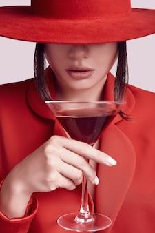 Elegante mujer hermosa en un traje rojo de moda y sombrero con cóctel