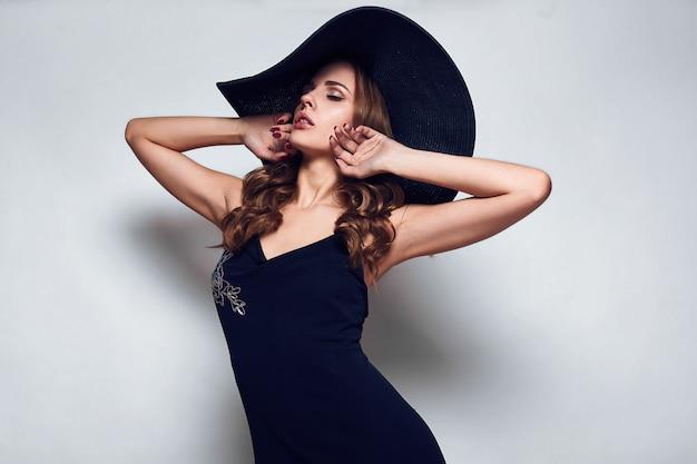 Elegante mujer hermosa en un vestido negro y sombrero