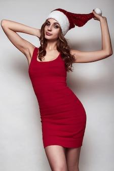 Elegante mujer hermosa en un vestido rojo y un sombrero de navidad