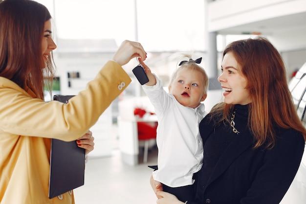 Elegante mujer con hija pequeña en un salón del automóvil