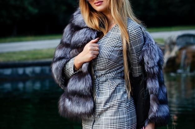 Elegante mujer joven en abrigo de pieles y vestido corto posando al aire libre.