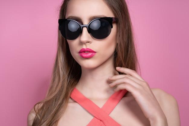 Elegante mujer joven en un bonito traje rosa y gafas de sol posando en rosa