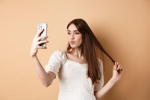 Elegante mujer joven jugando con el cabello y tomando selfie en el teléfono inteligente, hacer fotos para las redes sociales, de pie sobre fondo beige.