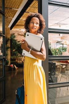 Elegante mujer joven de pie cerca de la entrada del restaurante con portátil