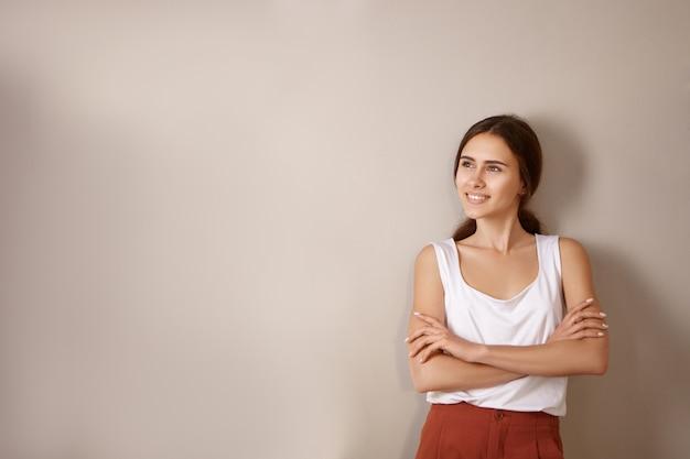 Elegante mujer joven relajada con hombros descubiertos y cabello oscuro recogido sentada cómodamente en un sillón tejido tocando su rostro y con interés, como si escuchara una historia
