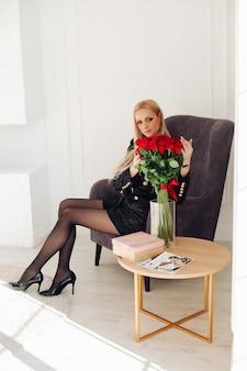 Elegante mujer joven sentada en un sillón y tocando el ramo de rosas rojas en un jarrón
