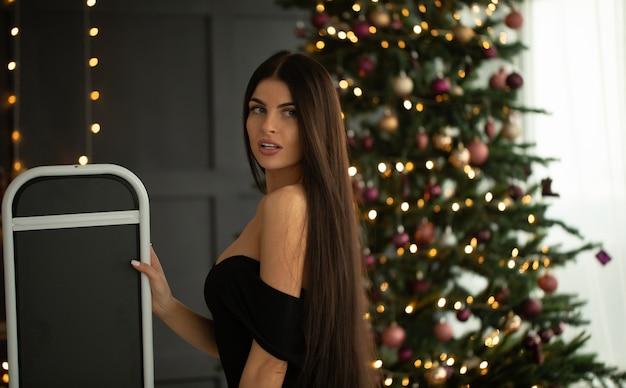 Elegante mujer joven en vestido de noche negro posando en el interior.