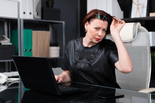 Elegante mujer levantó sus gafas y se ve bien sentado a la mesa en la oficina