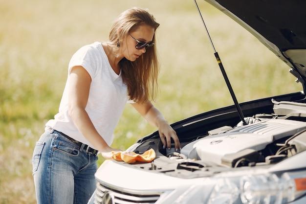 Elegante mujer limpia el auto con un trapo