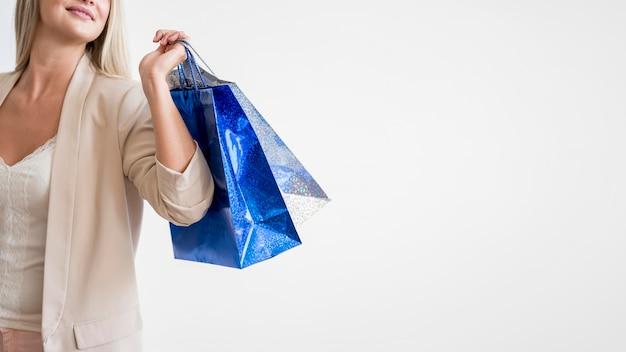 Elegante mujer llevando bolsas de compras con espacio de copia