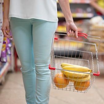 Elegante mujer llevando carrito de compras con frutas