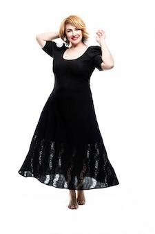 Elegante mujer de mediana edad sonriente en un vestido negro volando sobre una pared blanca. estilo de vida saludable y actividad. vertical.