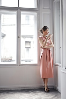 Elegante mujer mirando por la ventana