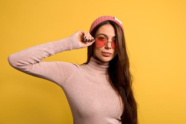 Elegante mujer moderna con pelo largo y liso con camisa rosa y gorra tocando sus gafas rosas redondas y sonriendo