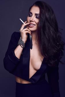 Elegante mujer morena caliente fumando un cigarrillo