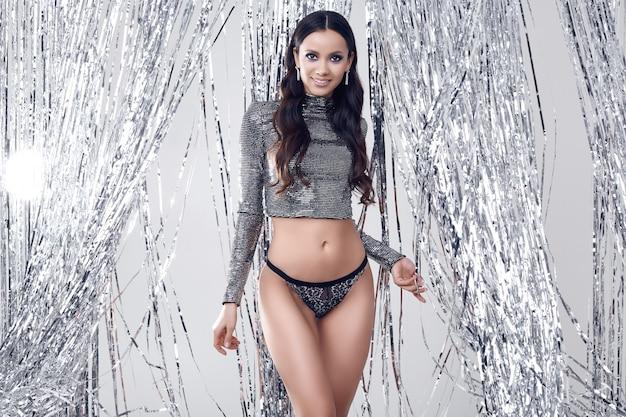Elegante mujer morena con cuerpo perfecto en lujoso top de lentejuelas