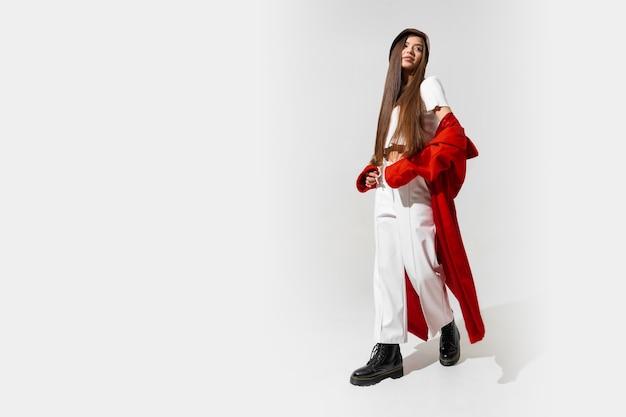 Elegante mujer morena europea en abrigo rojo y sombrero negro posando en la pared blanca